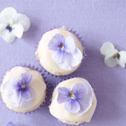 Mini Coconut Cupcakes with Passion Fruit Icing Recipe - These mini coconut cupcakes topped with passion fruit icing and edible flowers are a tropical addition to your dessert repertoire.