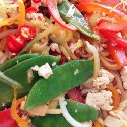 Spicy Tofu Stir Fry Recipe - Tofu, rice noodles, bell peppers, and snow peas are stir fried and spiced with a chili garlic paste to make this recipe for spicy tofu stir fry.