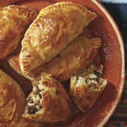 Argentinian Beef Empanadas Recipe - Beef, raisins, and olives make a flavorful mix inside a toasty pocket of bread for easy transportation and even easier eating.
