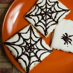 Spider Web S'mores Recipe - Graham crackers are topped with marshmallow fluff and decorated with chocolate in the shape of spider webs in these Halloween-inspired s'mores.