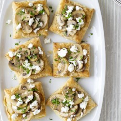 Mini Mushroom and Goat Cheese Tarts Recipe - Puff pastry squares are baked to a golden brown and served topped with mushrooms and goat cheese.