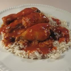 Dutch East Chicken Wings and Rice Recipe - Chicken wings are baked in a spicy tomato-based sauce. The accompanying rice is flavored with turmeric, cloves, almonds, and golden raisins.