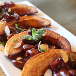 Cheeky Cherry Acorn Squash Recipe - Roasted wedges of spiced acorn squash are served with a sweet and tangy cherry-cranberry brandy sauce and topped with cinnamon-almond slivers.