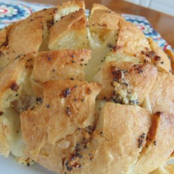 Sourdough Cheese Bread Recipe - Your guests will have fun pulling this yummy, gooey appetizer apart into servings. A round of sourdough bread is cut almost through into a checkerboard pattern, and seasoned butter is poured on. Swiss cheese goes in between the cuts in the bread, and the appetizer is baked until golden and bubbly.
