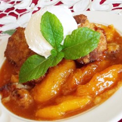 Fresh Southern Peach Cobbler Recipe and Video - Sweet Georgia peaches are topped with homemade biscuits creating a bubbling Southern-style peach cobbler perfect for summer nights.