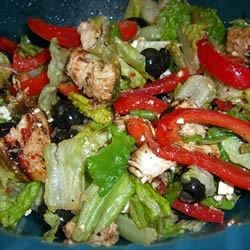 Mediterranean Chicken Salad Recipe - Tender, boneless chicken breasts are marinated in sun dried tomato dressing, grilled with sweet bell peppers, and served atop a crunchy romaine bed sprinkled with feta and olives.