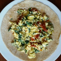 Spinach Feta Egg Wrap Recipe - Spinach, sun-dried tomato, and feta cheese are scrambled with eggs and wrapped in a warm tortilla to produce this delicious breakfast wrap.