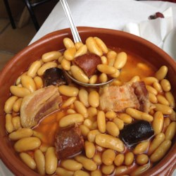 Fabada Recipe - This traditional Spanish meat and bean dish comes from the Asturias region. Spanish chorizo and morcilla sausages are slowly simmered along with salt pork and serrano ham yielding a rich and hearty saffron-flavored main course!
