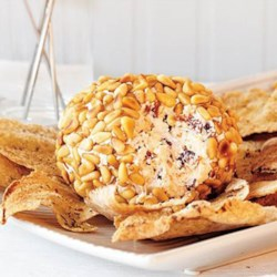 Greek-Style Cheese Ball Recipe - A variety of cheeses and herbs are rolled into balls and coated in pine nuts for a Greek-inspired cheese ball perfect for Christmas parties.