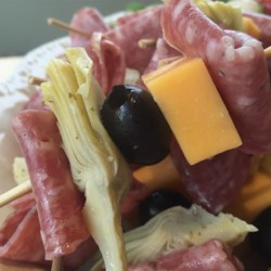 Antipasto on a Stick Recipe - Salami, mozzarella cheese, artichoke hearts, and olives are threaded on a toothpick and drizzled with olive oil for an Italian-inspired antipasto-on-a-stick appetizer.