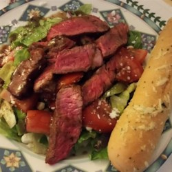 Grilled Steak Salad with Asian Dressing Recipe - Seasoned rib eye steak is grilled to a tender medium-rare and served sliced over a colorful salad of romaine, avocado, carrot, and cucumber. The spicy rice vinegar dressing adds a tangy Asian-style flavor.