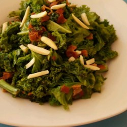 Kale Garlic Saute Recipe - Garlic and kale are sauteed and topped with bacon and cashews for a quick and easy side dish.