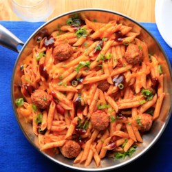 Simple Smokey Penne and Meatballs Recipe - Penne with prepared meatballs simmered in a marinara-BBQ sauce combo is topped with green onions, Cheddar cheese, and cilantro.