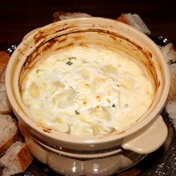 Hot Artichoke Dip Recipe - In this dip, canned artichoke hearts are mixed with green onions, pimento, mayonnaise, Parmesan cheese and whipped cream and baked in a casserole.  Serve fresh from the oven with baguette slices or crackers.