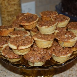 Pecan Pie Tarts Recipe -  These dainty treats are so easy to accomplish. The cream cheese pastry is mixed, rolled into balls and each pressed into the bottom and sides of tiny tart pans. The pecan filling is spooned in and the pies baked until the filling is set. Garnish each with a dollop of whipped cream and a pecan half.
