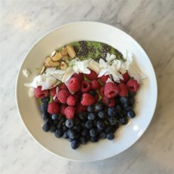 Green Smoothie Bowl Recipe - A green smoothie is topped with berries, chia seeds, granola, and coconut in this colorful and hearty green smoothie bowl.
