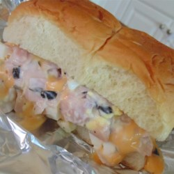 Hambuns Recipe - Whip up deliciously easy ham and cheese sandwiches flavored with green onions, olives, eggs and mayonnaise. Wrapped in foil and baked, they are great served hot or cold.