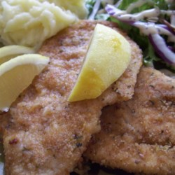 Baked Chicken Schnitzel Recipe - Thin pieces of chicken are coated in a zesty lemon breading and baked in this quick and easy baked chicken schnitzel recipe.
