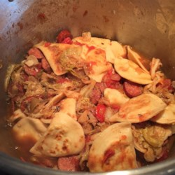 Cabbage, Polish Sausage, and Pierogies Recipe - Buttered savoy cabbage cooks with onions and kielbasa until tender. Pierogies are first boiled, then pan fried until golden brown before being stirred into the cabbage.