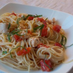Summer Pasta Toss II Recipe - A warm infusion of olive oil and Italian-style salad dressing is added to hot spaghetti to season the noodles. Toss with chopped tomatoes and chicken, then serve immediately with a dusting of Parmesan cheese.