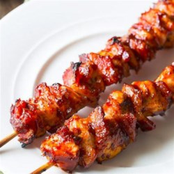 Chipotle BBQ Chicken Skewers Recipe - Skewers of chicken chunks, alternated with thick-cut pieces of bacon, are grilled and basted with a sweet and spicy sauce.