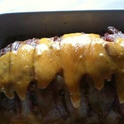 Dad's Cheesy Bacon Wrapped Meat Loaf Recipe - Meat loaf that is covered in bacon and oozing with Cheddar cheese is sure to be a crowd pleaser!