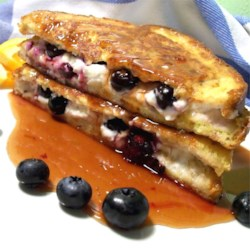 Easy Blueberries And Cream French Toast Sandwich with Orange Maple Syrup Recipe - Fresh blueberries and cream cheese are sandwiched between two slices of whole wheat bread and topped off with homemade orange maple syrup.