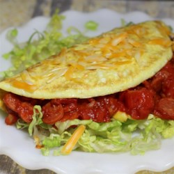 Pepperoni Pizza Omelet Recipe - Tomato sauce, pepperoni, olives, and mushrooms are cooked inside eggs in this quick and easy pepperoni pizza omelet recipe.
