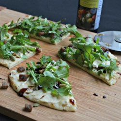 Arugula and Hummus Mini Pizzas Recipe - Arugula, hummus, dates, and pumpkin seeds are layered onto naan bread for a tasty and vegan pizza.