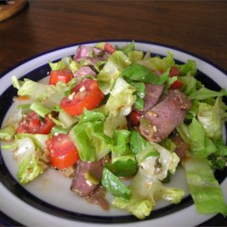 Steak Salad Recipe - Seared sirloin and a light vinaigrette top this crunchy, refreshing salad of romaine with tomatoes, peppers, red onion, green olives and blue cheese.