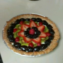 Banana Kiwi Strawberry Tart Recipe - A homemade tart shell is filled with a creamy custard, chilled, and topped with fresh fruit slices.