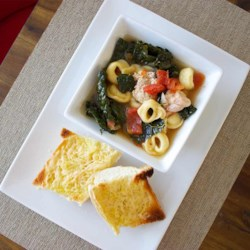 Hearty Chicken and Tortellini Stew with Cheesy Garlic Bread Recipe - This is a hearty one-pot stew made with chunks of chicken, Swanson(R) Chicken Broth, tortellini, kale and tomatoes goes great with toasted garlic and cheese baguette slices.