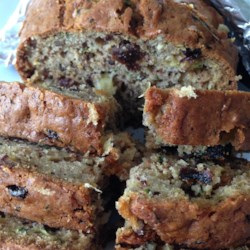 Zucchini Pineapple Bread Recipe - Moist zucchini bread is loaded with bits of pineapple, raisins, and walnuts.