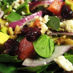 Harvest Salad Recipe - This spinach salad is adorned with blue cheese, avocado, and cranberries, then drizzled with a raspberry walnut vinaigrette.