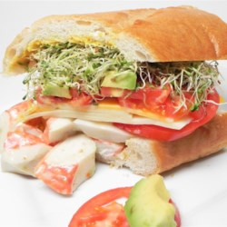 Super Crab Sandwich Recipe - A loaf of French bread stuffed with a tasty surimi filling, plus sprouts and cheese, tomato, and avocado slices makes great football game-watching fare.