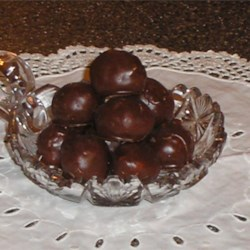 Bonbons Recipe - A sweet mixture of coconut, walnuts, sugar, margarine and condensed milk are rolled into little balls and dipped in chocolate to make these decadent frozen treats.