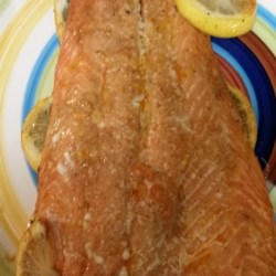 Grilled Steelhead Trout Recipe - This simple preparation of steelhead trout calls for a sauteed, lemon-kissed mixture of garlic and onion to be brushed atop the fish as it grills on a bed of lemon slices.