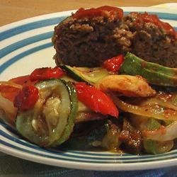 Beef Loaf Deluxe Recipe - Baked meat loaf with roasted green pepper, red pepper, onion, and potatoes, smothered with tomato sauce.