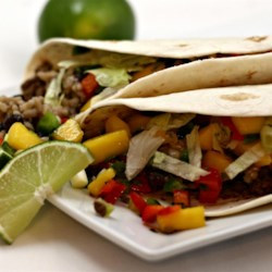 Beef Soft Tacos with Mango Salsa Recipe - This recipe delivers three components -- seasoned ground beef, mango salsa, and black beans with rice -- to be used for filling soft taco shells.