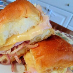 Ham and Swiss Sliders Recipe - Honey mustard adds great flavor to these buttery ham and Swiss cheese sliders. Serve with coleslaw or chips at your next family gathering!