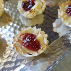 Brie Cups Recipe - Brie cheese is topped with raspberry preserves in this quick, easy, and sophisticated bite-sized brie cup appetizer.