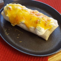 Smothered Burritos Recipe - Beef and refried bean burritos are baked under a creamy sauce topped with cheese in this easy smothered burritos recipe.