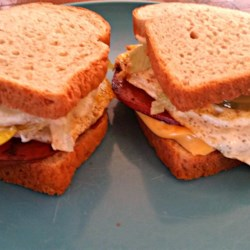 Kevin's Toasted Honey Wheat Berry Bologna and Egg Sandwich Recipe - Sweet onions and pickles finish off this heaping sandwich.
