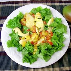 Warm Chicken and Mango Salad Recipe - Spicy chicken and mangoes are mixed with a tangy dressing and served over romaine lettuce.