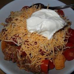 Corn Chip Salad Recipe - All the standard taco salad fixings (ground beef, lettuce, tomatoes and onion) are chopped and tossed together with two kinds of cheese, purple kidney beans, Thousand Island dressing and a generous helping of corn chips to create a kaleidoscopic party-pleaser.