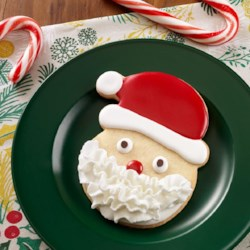 Santa Sugar Cookies Recipe - Santa-shaped rolled sugar cookies, decorated with red and white icing, have a fun Reddi-wip beard added just before eating.