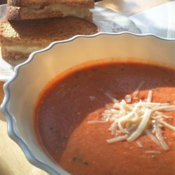 Spicy Tomato Bisque with Grilled Brie Toast Recipe - Nothing's more comforting than grilled cheese and tomato soup.  This is a gussied-up version, with grilled Brie cheese sandwiches and spiced tomato bisque with basil.  As the soup soaks into the sandwich, break into pieces with your spoon and ladle up with the soup.
