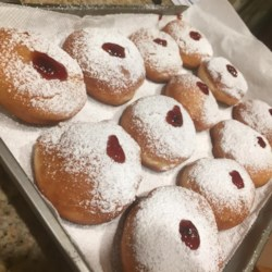 Sufganiot Recipe - Build a holiday brunch around these scrumptious homemade doughnuts. A rich yeast dough is cut into rounds, filled with sweetened cottage cheese or fruit preserves, fried in oil, and rolled in confectioners' sugar.
