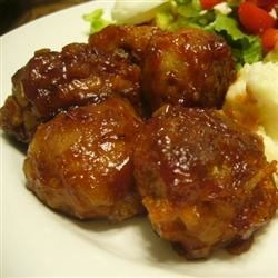 Barbecued Meatballs Recipe - Ground beef, bread crumbs, milk, onion, and egg are included in these baked meatballs. Home-made or bottled barbecue sauce is added for the final 35 minutes of cooking time.