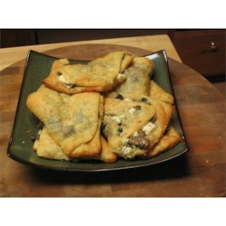 Flaky Crescent Mushroom Turnovers Recipe - If you love mushrooms, you'll love this easy hot appetizer. Sauteed mushrooms are baked with cheese inside a flaky crust. Poppy seeds may be used in place of sesame seeds.